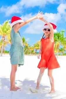 Miúdos adoráveis no chapéu de santa durante férias da praia do natal. ano novo na praia