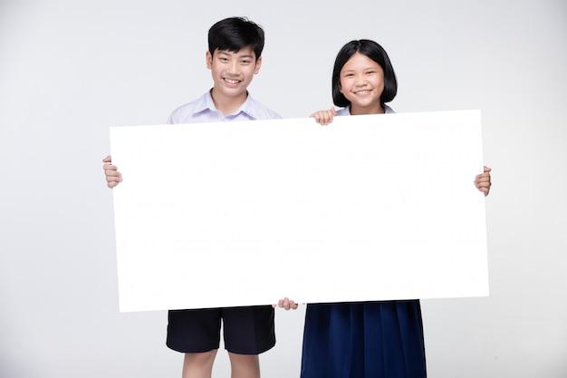 Miúdos asiáticos bonitos no uniforme do estudante com placa branca.