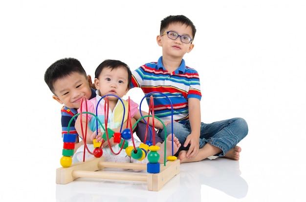 Miúdos asiáticos que sentam-se no assoalho, jogando com brinquedo.