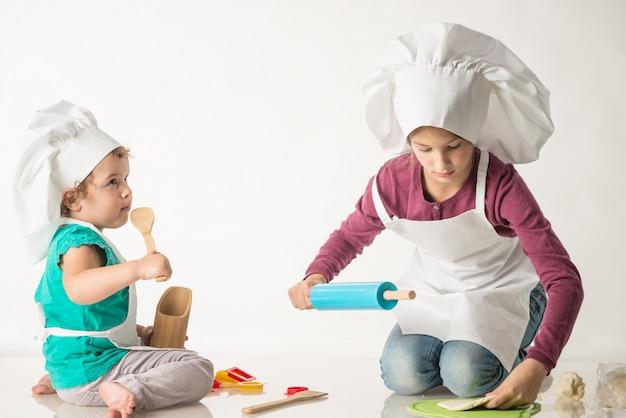 Miúdos bonitos em um terno de cozinheiro