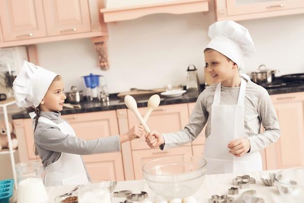 Miúdos bonitos jogam espadas de colheres de pau na cozinha.