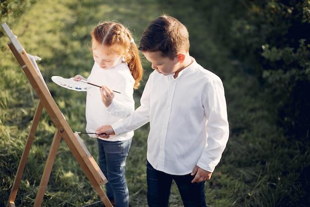 Miúdos bonitos que pintam em um parque