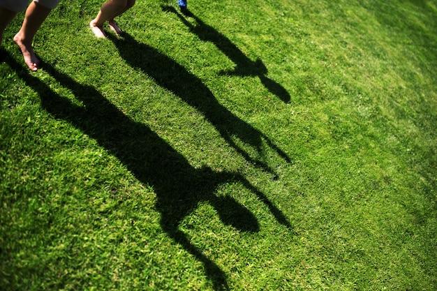 Miúdos com suas sombras na grama
