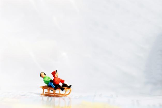 Miúdos diminutos que jogam o divertimento com slider da neve.