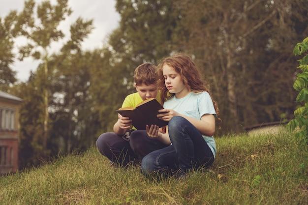 Miúdos espertos que lêem o livro ao ar livre.