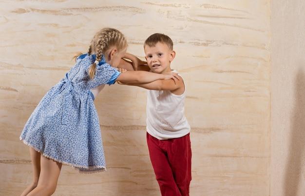 Miúdos fofinhos e brancos brincando em casa, isolados em paredes de madeira marrom claro