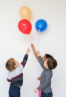 Miúdos pequenos bonitos com balões