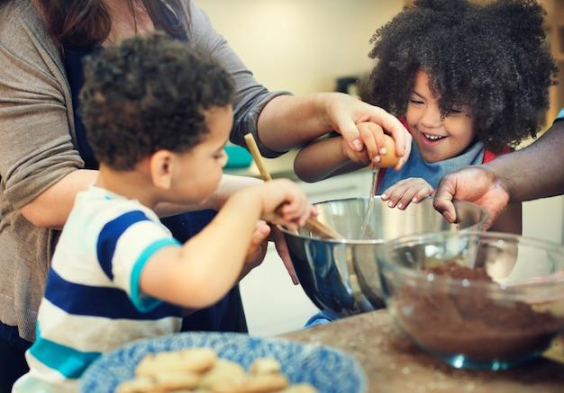 Miúdos que cozinham o conceito da cozinha dos biscoitos do cozimento