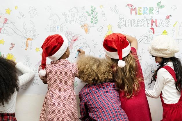 Miúdos que desenham em uma decoração de natal