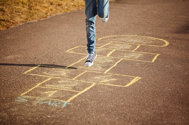Miúdos que jogam amarelinha no campo de jogos ao ar livre. jogo de rua popular amarelinha