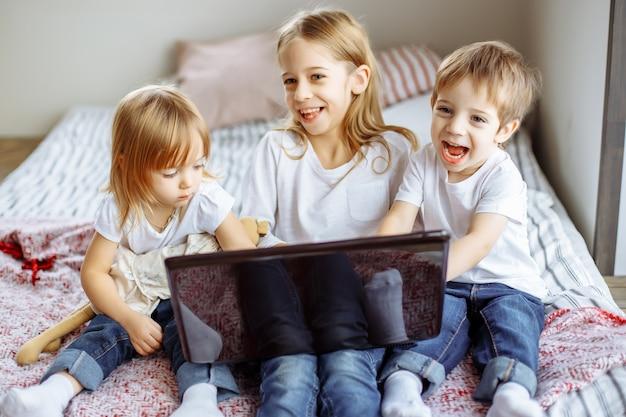 Miúdos que jogam com computador portátil em casa