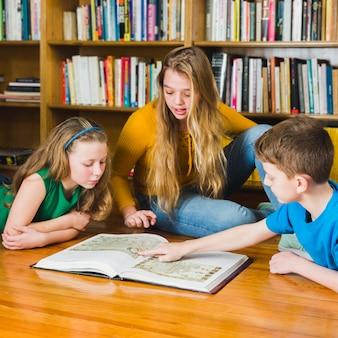 Miúdos que olham retratos no livro da biblioteca