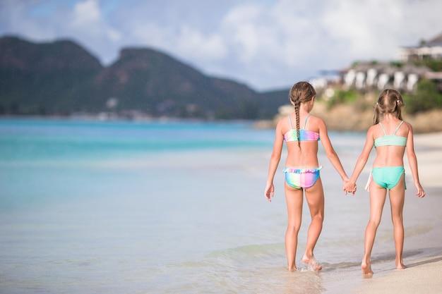 Miúdos que têm o divertimento na praia tropical durante as férias de verão que jogam junto.