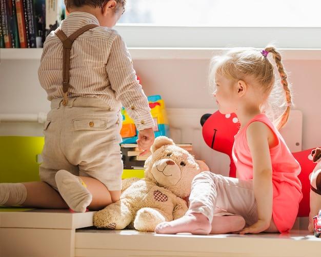 Miúdos sentados na janela com brinquedos