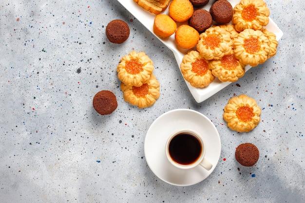 Mix de biscoitos doces, rolo de bolo, mini cupcakes.