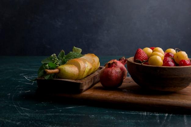 Mix de frutas em uma bandeja de madeira isolada no espaço azul