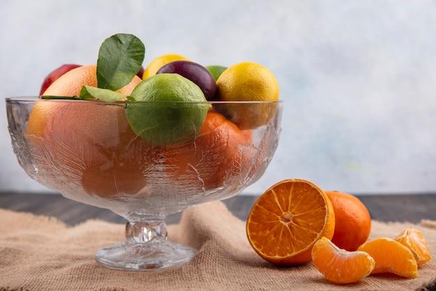Mix de frutas, limões, limas, ameixas, pêssegos e laranjas em um vaso em um guardanapo bege
