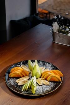 Mix de salada de frutas, sobremesa de frutas - banana fatiada, tangerina, laranja, maçã. frutas picadas em uma placa preta. uma sobremesa saborosa e saudável. vista superior