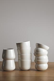 Mix de vista lateral de diferentes xícaras de café simples brancas em branco em pirâmide na mesa de madeira grossa isolada