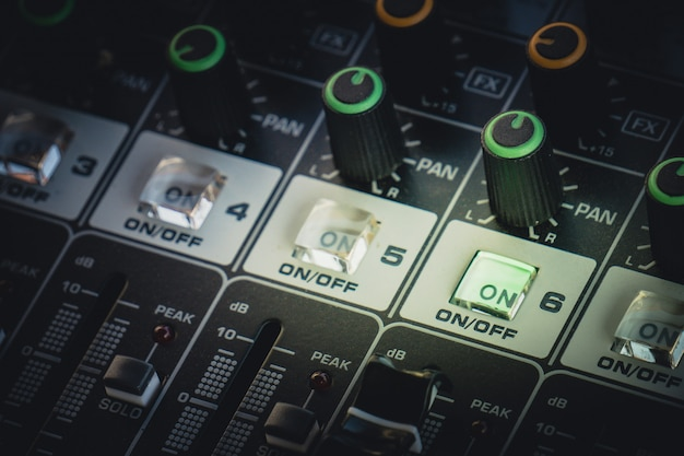 Mixer de áudio profissional com botões e barras deslizantes para ajustar o som