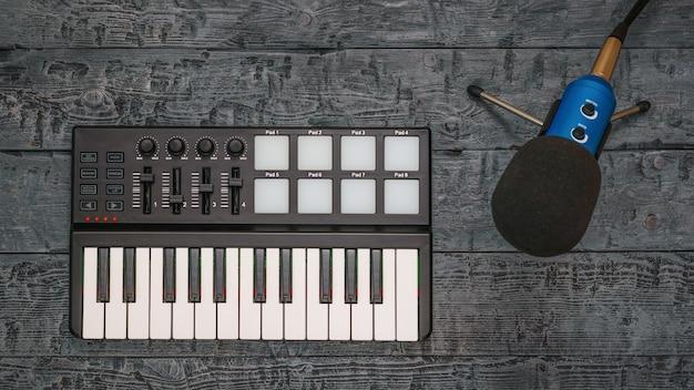 Mixer de música eletrônica e microfone de fio em uma mesa de madeira