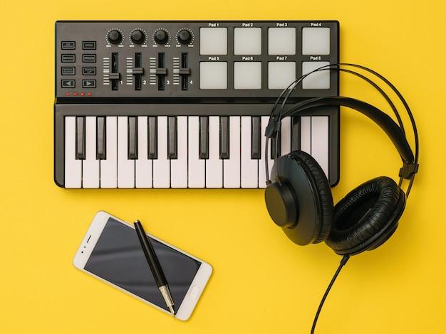 Mixer de música, smartphone, fones de ouvido e caneta em fundo amarelo. o conceito de organização do local de trabalho. equipamentos para gravação, comunicação e escuta musical.