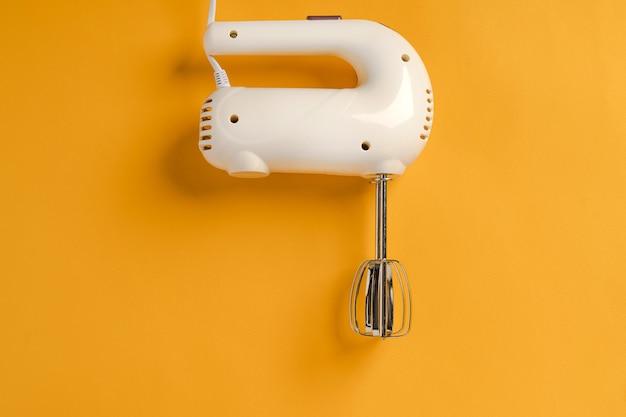 Mixer para bater com dois batedores em um fundo amarelo o conceito de minimalismo