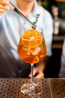 Mixologist decora alecrim no coquetel de frutas laranja que se mistura com fatias de laranja e lichia em um copo de vinho.
