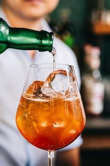 Mixologist derrama licor sobre o coquetel de frutas laranja que misturam com fatias de laranja em um copo de vinho.