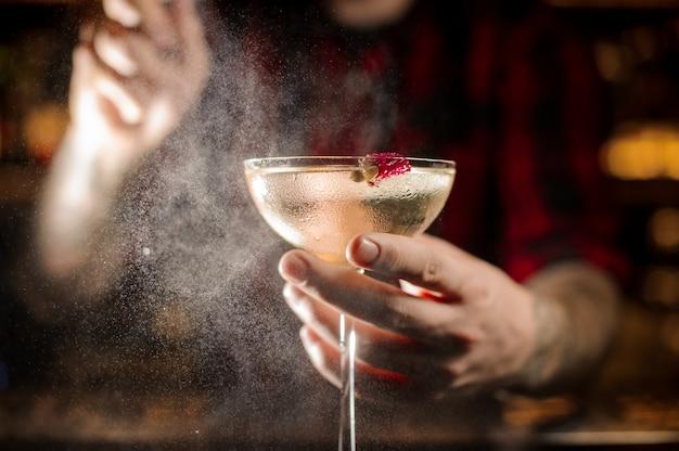 Mixologist espirrando amargo no copo de cocktail elegante