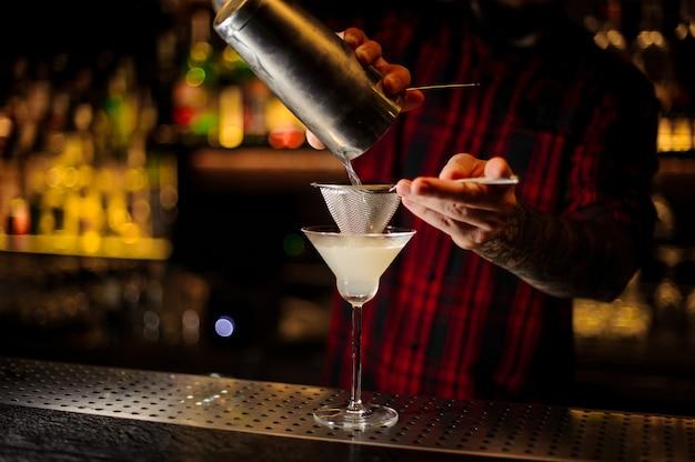 Mixologista servindo bebida fresca e azeda em um copo de coquetel usando shaker e peneira