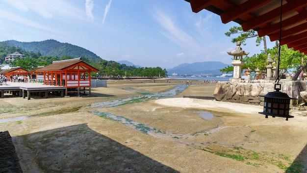 Miyajima, japão - setembro 2016: turistas caminhando na praia quando a maré baixa no santuário de itsukushima