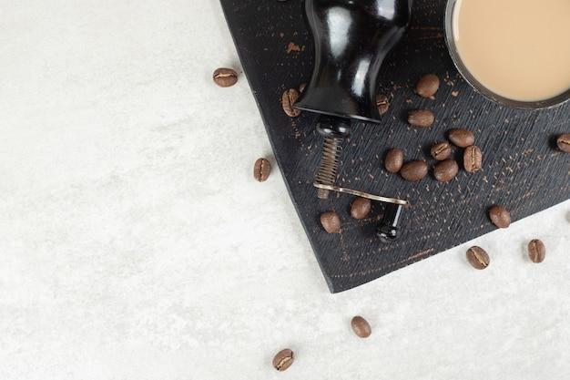 Moagem de cafeteira, café e grãos no quadro escuro