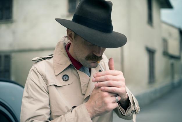 Mobster acendendo um cigarro enquanto espera na frente de seu carro antigo