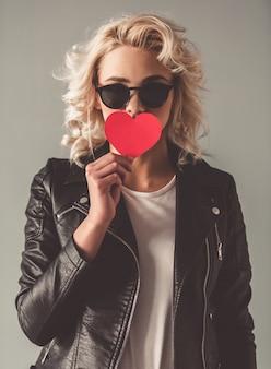 Moça à moda em jaqueta de couro e óculos de sol.