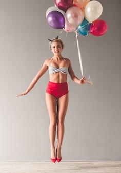 Moça à moda na roupa do verão que guarda balões.