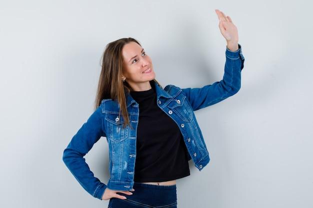 Moça acenando com a mão para se despedir de blusa, jaqueta e parecendo confiante. vista frontal.
