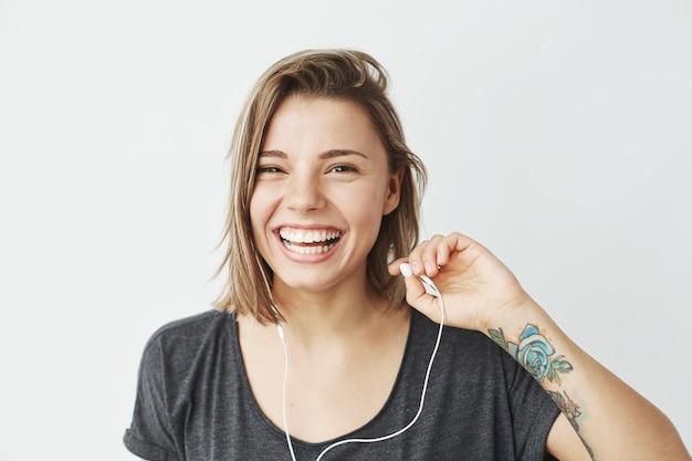 Moça agradável em fones de ouvido rindo.