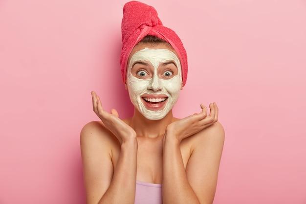 Moça alegre com expressão alegre, espalha as palmas das mãos perto do rosto, aplica máscara de argila natural para parecer revigorada, tem sorriso charmoso, enrolada em toalha de banho macia