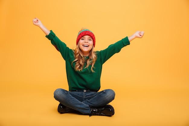 Moça alegre na camisola e chapéu, sentado no chão enquanto se alegra e olhando para a câmera sobre laranja