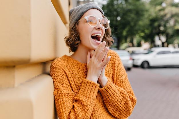Moça animada de chapéu cinza rindo na rua ao lado do prédio