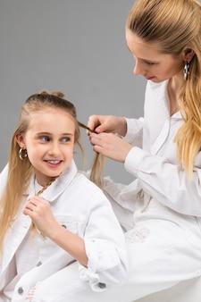Moça animada de jaqueta branca conversando com a irmã mais velha enquanto ela está ocupada com o penteado