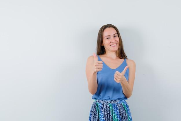 Moça aparecendo o polegar enquanto sorria na blusa, saia e olhando alegre, vista frontal.