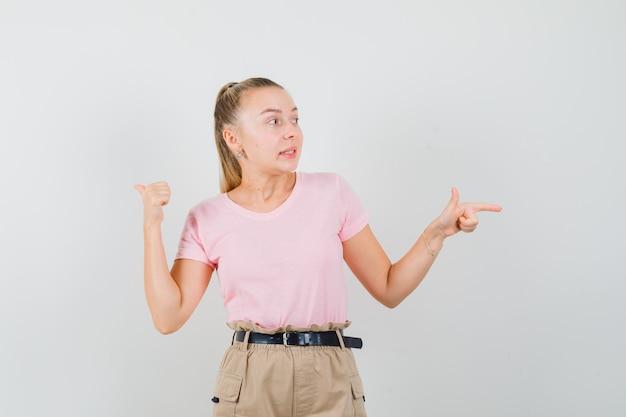 Moça apontando para o lado e para trás em camisetas e calças e parecendo indecisa