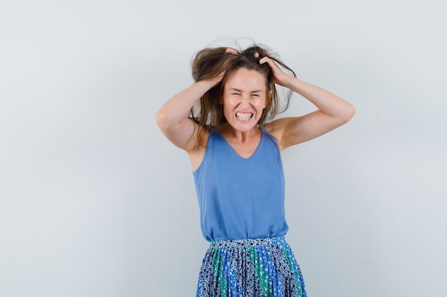Moça arrancando o cabelo na camiseta, saia e parecendo animada. vista frontal.
