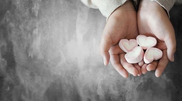 Moça asiática com doces de coração nas mãos. dia dos namorados.