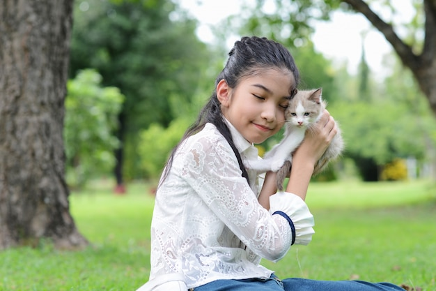 Moça asiática que guarda gatinhos no parque