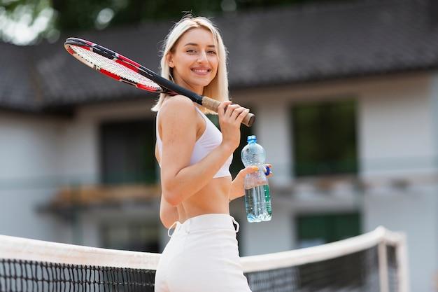 Moça ativa que guarda a garrafa de água