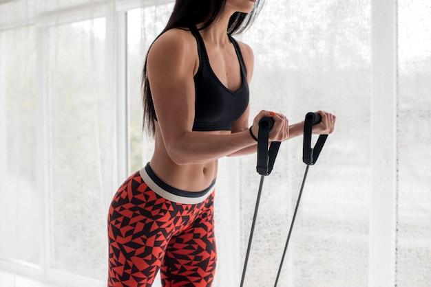 Moça atlética que faz a aptidão no estúdio em uma luz de fundo. fitness, estilo de vida saudável