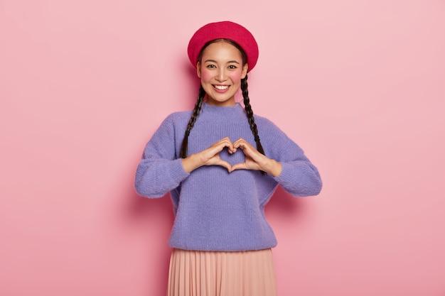 Moça atraente com aparência agradável, faz gesto de coração sobre o peito, confessa que está apaixonada, usa boina vermelha, suéter roxo enorme, tem maquiagem, isolada em parede rosa
